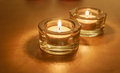 Two tea light candles in glass on gold burning golden background Stock Image