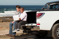 Two is a team young caucasian men and dwarfish african men sitting on the back of pickup truck working on laptop Royalty Free Stock Photo