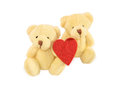Two teddy bears sitting with red felt heart on white. Royalty Free Stock Photo