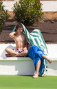 Two teen boys sitting on a bench at the pool under towel Stock Photos