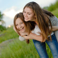 Two teen girl friends laughing having fun in spring or summer outdoors green background Stock Photos