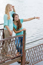 Two teen girl friends looking over water on summer day sea or river Royalty Free Stock Photo