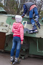 Two teen girls with rollers at war Bradley fighting vehicle Royalty Free Stock Photo