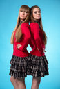 Two teen schoolgirls stand back to back over blue background studio Royalty Free Stock Photography