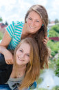 Two teen young women friends laughing in spring or summer outdoors girl having fun background Stock Photography