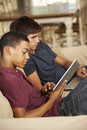 Two Teenage Boys Sitting On Sofa At Home Using Tablet Computer And Laptop Royalty Free Stock Photo