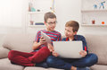 Two teenage boys using tablet on couch at home Royalty Free Stock Photo