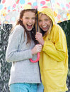 Two teenage girl sheltering from rain beneath umbrella smiling to camera Stock Photo