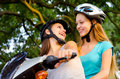 Two teenage girlfriends riding scooter on sunny summer day Royalty Free Stock Photography