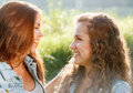 Two teenage girls close up of outdoors in jeans wear happy smiling looking at each other Stock Photography