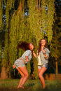 Two teenage girls dancing outdoors having good time full length Stock Photo