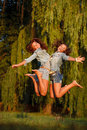 Two teenage girls jumping outdoors full length Royalty Free Stock Image