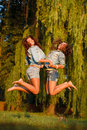 Two teenage girls jumping outdoors holding hands Stock Images