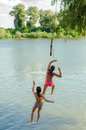 Two teenage girls jumping into the river Royalty Free Stock Photo