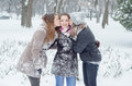 Two teenage girls kissing their girlfriend on snowy winter day Royalty Free Stock Photo