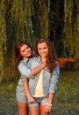 Two teenage girls outdoors in jeans wear hugging looking at camera Royalty Free Stock Photography