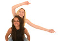 Two teenage girls portrait of one multi racial and one white caucasian playfully enjoying each others company white background Stock Photography