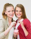 Two teenage girls putting money into piggy bank smiling to camera Royalty Free Stock Photo