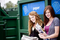 Two teenage girls standing next to a recycling container for paper Royalty Free Stock Photo