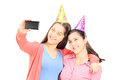 Two teenage girls taking pictures of themselves with cell phone isolated on white background Royalty Free Stock Photo