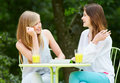 Two teenage girls using digital tablet in outdoor cafe with and mobile phone café smiling Royalty Free Stock Photo