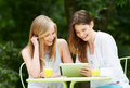 Two teenage girls using digital tablet in outdoor cafe with and mobile phone café smiling Stock Photography