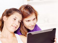 Two teenage girls using tablet computer Stock Images