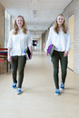 Two teenage girls walking in long school corridor carrying text books Royalty Free Stock Photo
