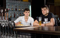 Two teenage men drinking at the pub young sitting counter in bar enjoying a pint of beer Royalty Free Stock Images