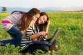 Two teenager girls with laptop computer in nature Royalty Free Stock Photography
