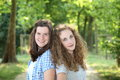 Two teenager girls smiling and posing back to back pretty healthy on an alley in a green forested area in summer Royalty Free Stock Photo