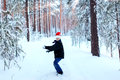 Two teenagers in christmas hats santa claus having fun in the sn snow covered forest playing snow Royalty Free Stock Photo