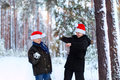 Two teenagers in christmas hats santa claus having fun in the sn snow covered forest playing snow Stock Image