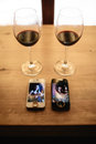 Two telephones, rings and two glasses of wine on a table