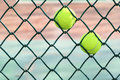 Two tennis balls the in wire grid Stock Photos