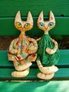 Two textile toy cats with big expressive eyes are sitting on a green bench on a sunny summer day. Royalty Free Stock Photo