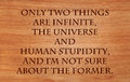 Only two things are infinite the universe and human stupidity i m not sure about former quote by albert einstein on wooden Stock Images