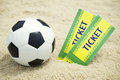 Two tickets and football soccer ball on brazilian beach to event stand with Stock Photos