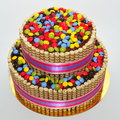 Two tier chocolate decorated with finetti sticks and colorful candy fondant cake bombons vanilla Stock Photo