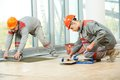 Two tilers at industrial floor tiling renovation tiler builder worker installing tile repair work Royalty Free Stock Photography