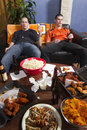 Two tired men after watching sports game on tv vertical couch upset and sick from all the junk food while Stock Photo