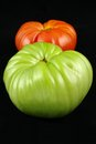 Two tomatoes ripe and unripe tomato on a black background Royalty Free Stock Photos