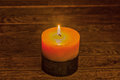 Two toned candlelight illuminating the wooden background burning candle on a table close up Royalty Free Stock Image