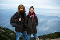Two tourists man and woman standing on a mountain top Royalty Free Stock Photo