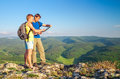 Two tourists on mountain read the map. Royalty Free Stock Photo