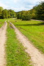 Two track dirt country road in caucasus mountains in early autumn day Royalty Free Stock Photo
