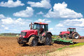 Two tractors on the field tractor plowing in spring day Royalty Free Stock Images