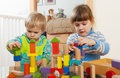 Two tranquil children playing with wooden toys in home interior Stock Photo