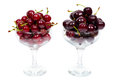 Two transparent glass bowl of ripe cherries and sweet isolated over white background Stock Photography