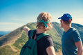Two travelers discuss about itinerary on the top of mountain hil hill Stock Photos